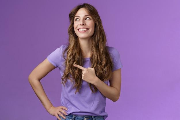 Une fille aux cheveux bouclés optimiste, enthousiaste et motivée, tourne à gauche, pointant sur le côté, contemple la prod ...