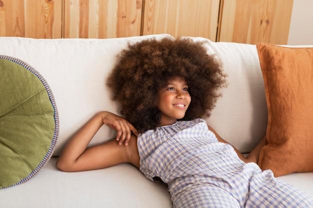 Fille aux cheveux bouclés se détendre sur le canapé