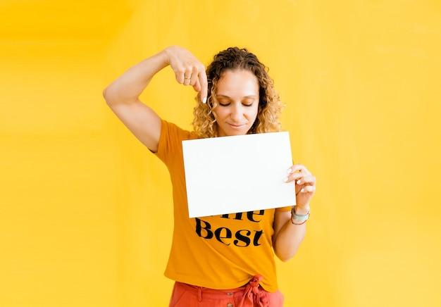 Fille aux cheveux bouclés tenant une carte vierge. isolé sur fond jaune portrait de femme souriante.