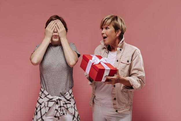 Fille aux cheveux brune fermant les yeux avec ses mains et posant avec une femme blonde en veste beige avec boîte-cadeau rouge sur fond rose.