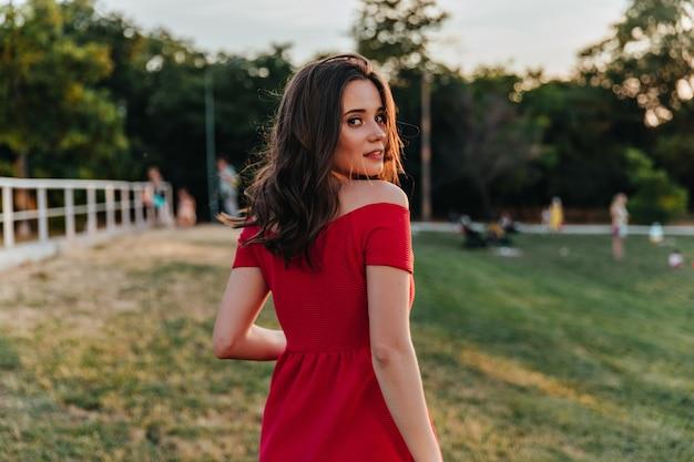 Fille aux cheveux bruns rêveuse regardant par-dessus l'épaule en marchant dans le parc. portrait d'une incroyable dame caucasienne en robe rouge debout.
