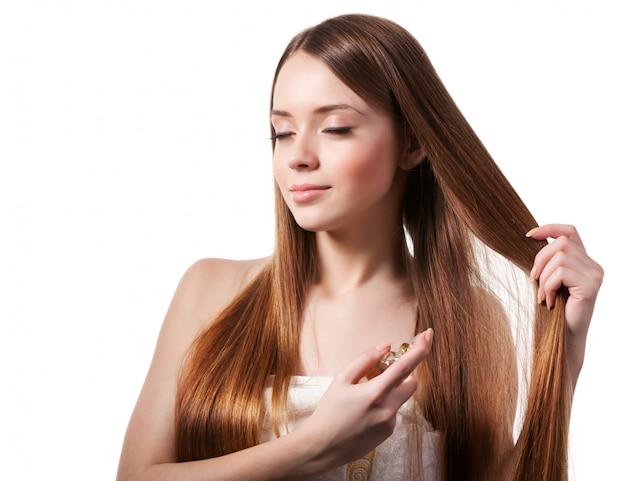 Fille aux cheveux bruns vaporisant du parfum sur son poignet