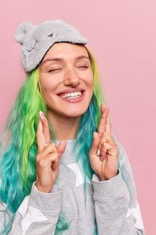Fille aux cheveux colorés teints perçants garde les doigts croisés fait désir souhaitable ferme les yeux vêtus de vêtements de nuit sleepmask isolated on pink