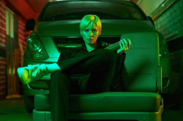 Une fille aux cheveux courts est assise dans le garage près de la voiture et tient une chauve-souris dans sa main photo moderne en n...