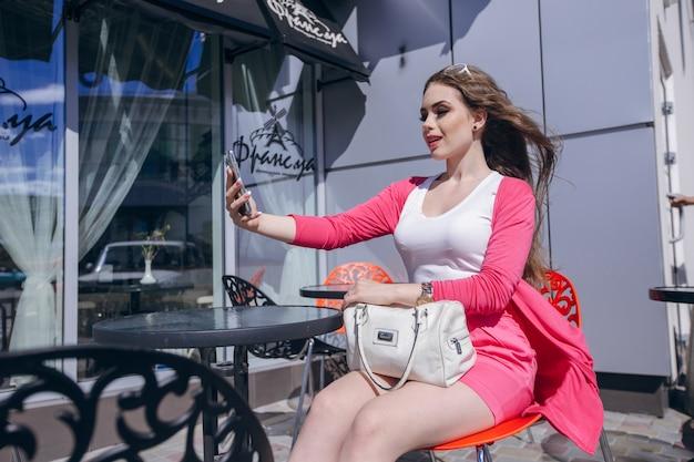 Fille aux cheveux dans le vent en regardant son téléphone