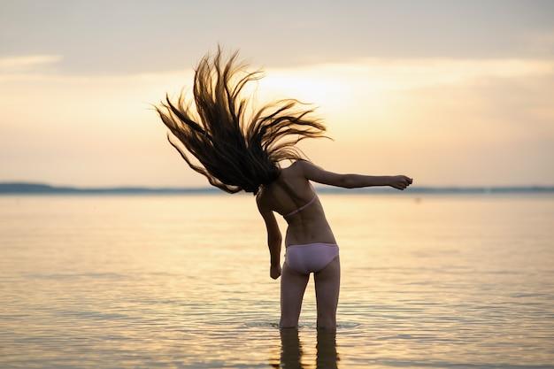 Fille aux cheveux dénoués sur la mer pendant le coucher du soleil