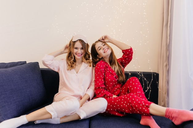 Fille aux cheveux longs en chaussettes roses, assise sur un canapé avec son amie. adorables jeunes femmes portent des costumes de nuit posant sur un canapé bleu.