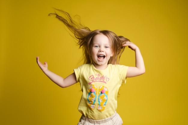 Fille aux cheveux longs en chemise mignonne jouant avec les cheveux et virevoltant