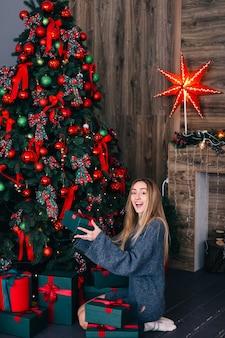 Fille aux cheveux longs dans un pull gris se trouve près d'un arbre de noël et tient un cadeau. cheminée avec guirlandes et étoile en arrière-plan.