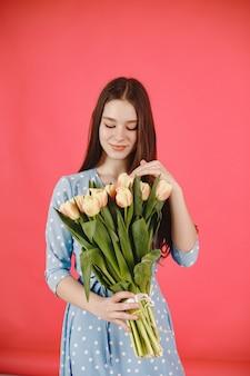Fille aux cheveux longs. femme avec un bouquet de fleurs. dame en robe bleue.