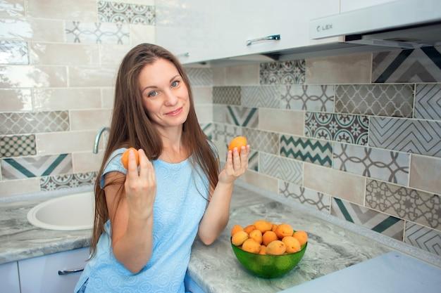 Une fille aux cheveux longs à la maison dans la cuisine trie les abricots mûrs
