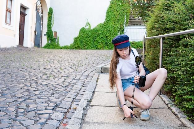 Une fille aux cheveux longs pose un trépied avec un téléphone dans la rue.