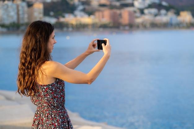 Une fille aux cheveux longs prend un selfie avec un fond de mer
