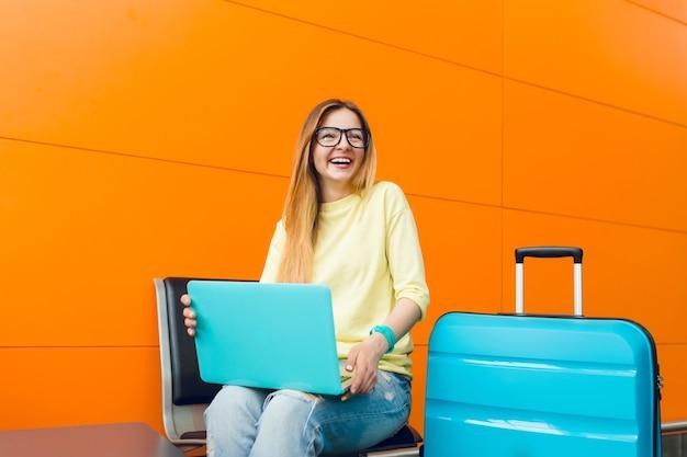 Fille aux cheveux longs en pull jaune est assise sur fond orange. elle a une valise bleue et un ordinateur portable. elle sourit heureuse.