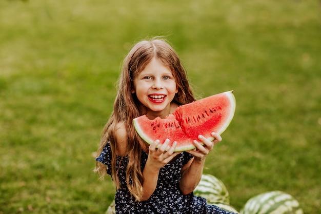 Fille aux cheveux longs en robe d'été bleue posant avec une grosse tranche de pastèque dans le jardin. espace de copie.