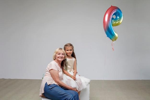 Fille aux cheveux longs en robe de fête avec sa grand-mère senior fond blanc tourné en studio familial