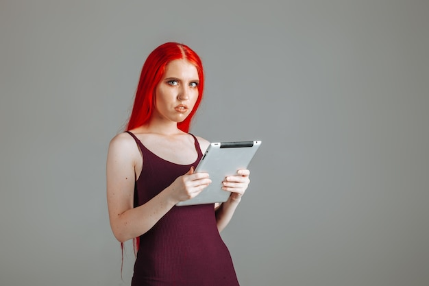Fille aux cheveux longs rouges looking at tablet