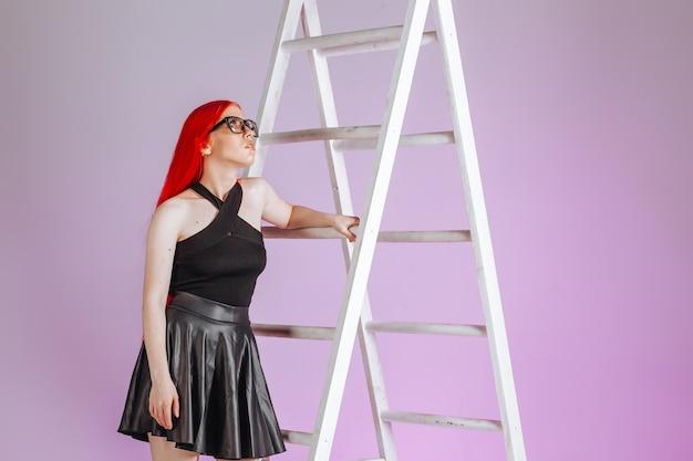 Fille aux cheveux longs rouges portant des lunettes et une jupe en cuir monte une échelle sur fond rose