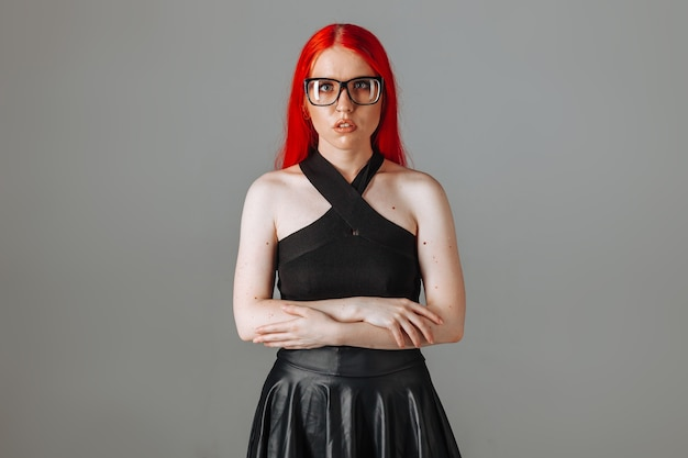 Fille aux cheveux longs rouges portant des lunettes et une jupe en cuir posant sur fond gris