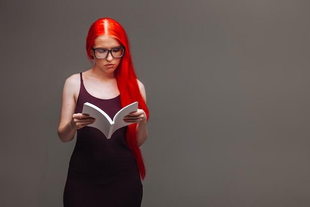 Fille aux cheveux longs rouges portant des lunettes avec un livre blanc