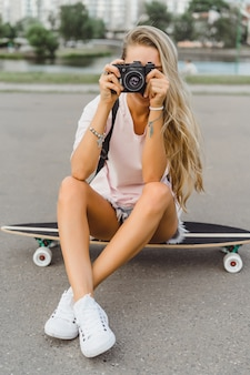 Fille aux cheveux longs avec skateboard photographiant à la caméra. rue, sports actifs