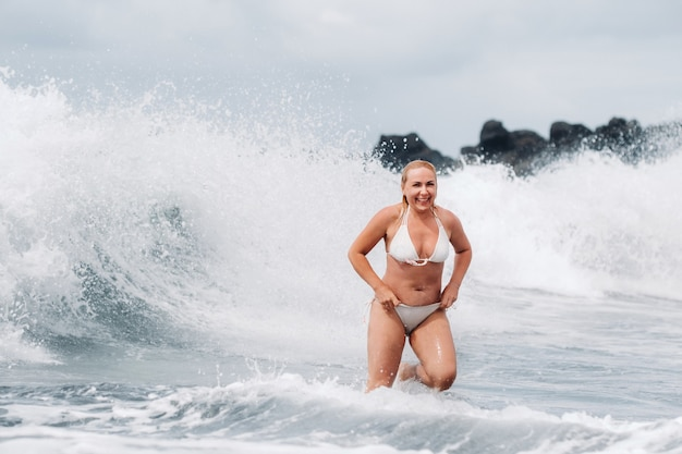 Une fille aux cheveux mouillés saute par-dessus de grosses vagues dans l'océan atlantique.
