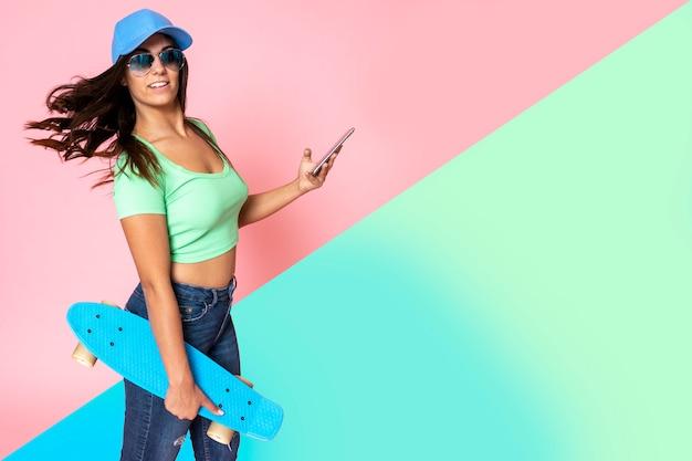 Fille aux cheveux noirs avec une casquette à la tête avec style fashion tenant une planche à roulettes et un téléphone