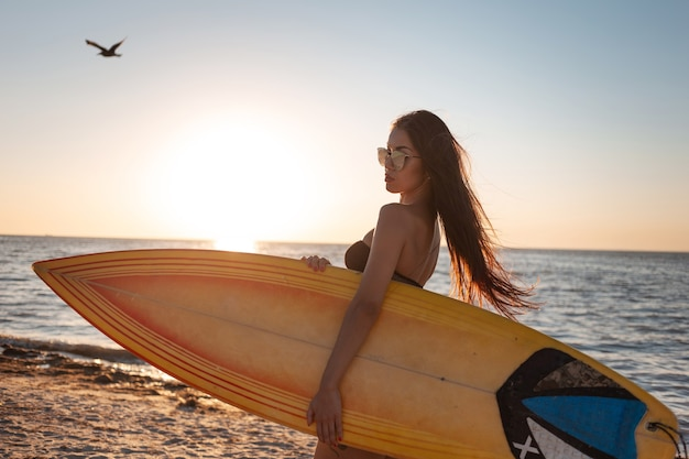 Une fille aux cheveux noirs en maillot de bain et lunettes de soleil se promène sur la plage de sable au coucher du soleil et tient une planche de surf.