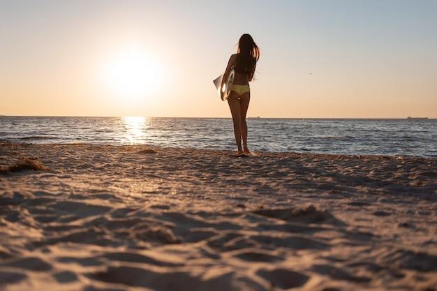 Une fille aux cheveux noirs en maillot de bain se dresse sur la plage de sable près de la mer au coucher du soleil et tient une planche de surf.