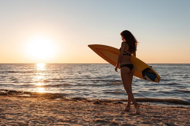 Une fille aux cheveux noirs en maillot de bain se promène sur la plage de sable près de la mer au coucher du soleil et tient une planche de surf.
