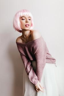 Fille aux cheveux rose clair posant en jupe blanche. photo intérieure d'une jeune femme européenne pensive porte une perruque courte.
