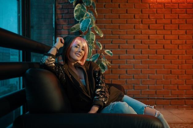 Fille aux cheveux roses assise détendue sur un canapé en cuir