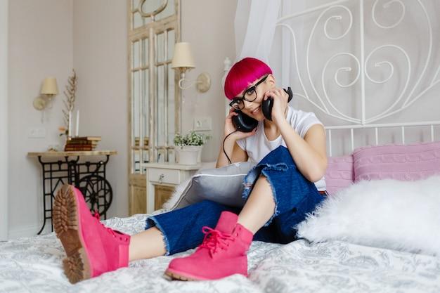 Fille aux cheveux roses écoute de la musique et se repose sur le lit