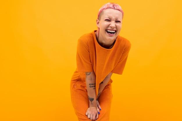 Fille aux cheveux roses et un visage percé vêtue d'une robe orange lâche sur jaune