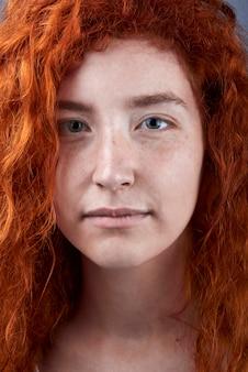 Fille aux cheveux rouge caucasienne avec des taches de rousseur et des yeux verts