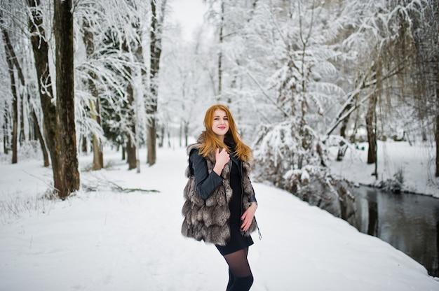Fille aux cheveux rouge en manteau de fourrure à pied au parc d'hiver enneigé.