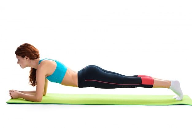 Fille aux cheveux rouges fait planche sur tapis de gym.