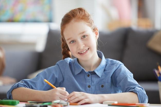 Fille aux cheveux rouges souriante, dessiner des images
