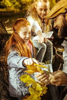 Une fille aux cheveux rouges souriante poiting aux feuilles que son professeur tient une bonne journée