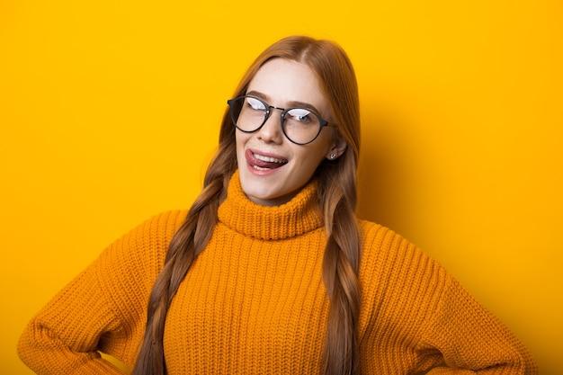 Fille aux cheveux rouges et taches de rousseur regarde à travers ses lunettes tout en posant sur fond jaune dans un pull