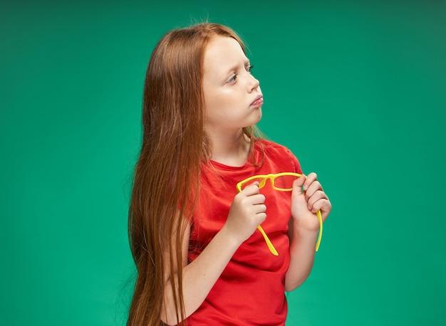 Fille aux cheveux rouges tenant des lunettes jaunes dans ses mains t-shirt rouge mur vert.