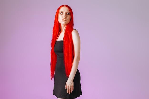 Fille aux cheveux rouges très longs sur fond rose