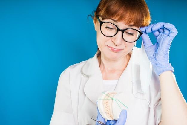 Une fille aux cheveux roux dans des lunettes et des vêtements médicaux regarde tristement un dispositif médical