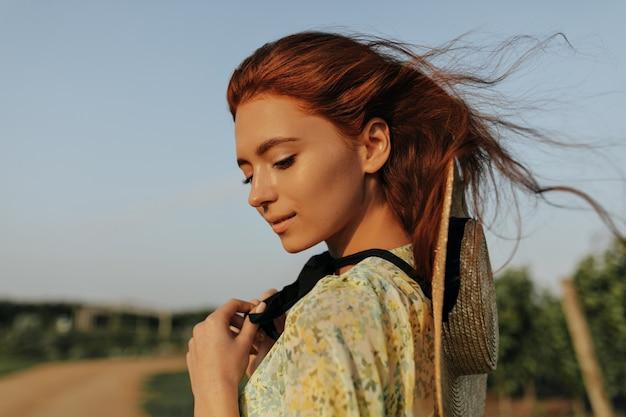 Fille aux cheveux roux avec de jolies taches de rousseur, un chapeau de paille et un bandage sombre sur le cou en tenue cool jaune regardant vers le bas et posant en plein air