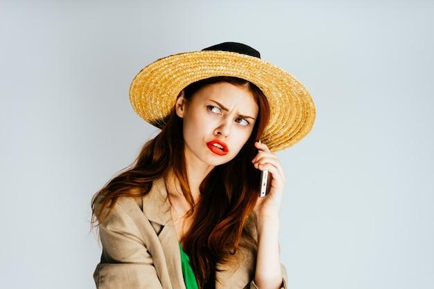 Fille aux cheveux roux maléfique dans un chapeau parlant au téléphone et détournant les yeux