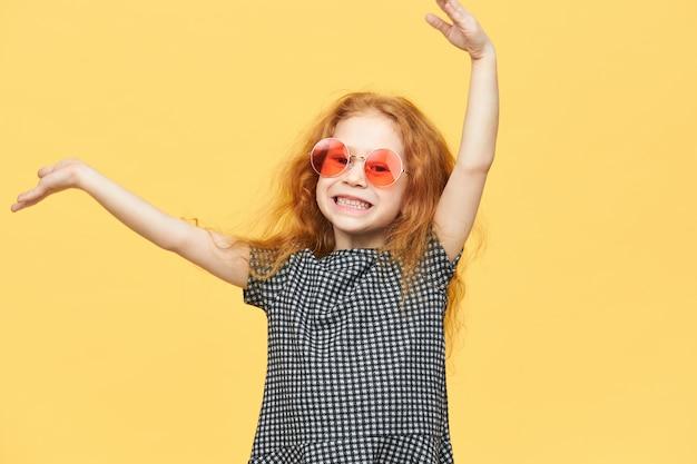 Fille aux cheveux roux avec une robe noire et blanche et des lunettes de soleil