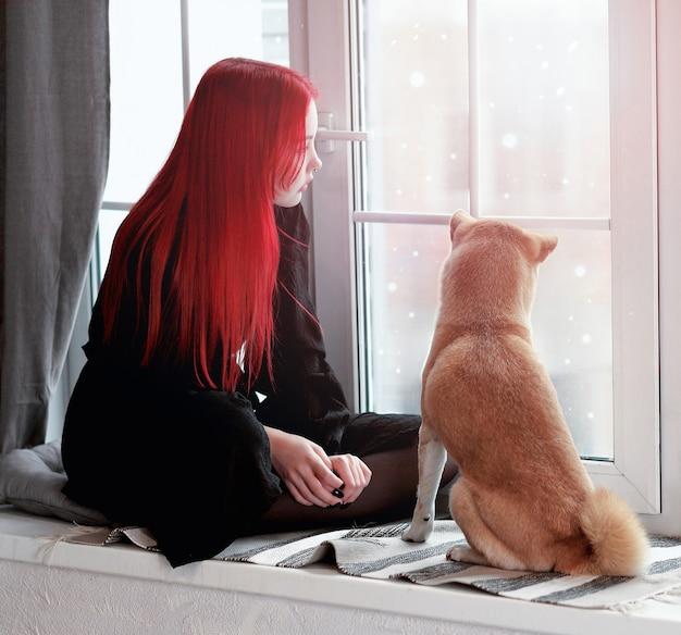 Une fille aux cheveux roux et à la robe noire est assise sur le rebord de la fenêtre avec son chien shiba inu