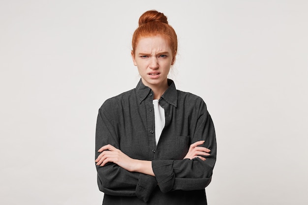 Une fille aux cheveux roux avec ses cheveux pliés en chignon se tient les bras croisés se sent dégoûtée