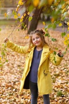 Une fille aux feuilles de bouleau. jolie petite fille dans un imperméable jaune.