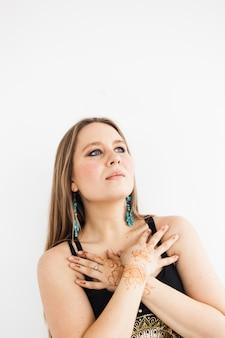Une fille aux longs cheveux blonds dans des vêtements sombres, la beauté, les soins personnels, le henné s'appuyant sur ses mains, les traditions